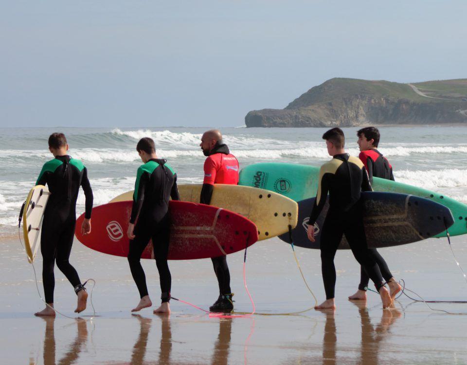 Profesor con alumnos hacia el mar con tablas