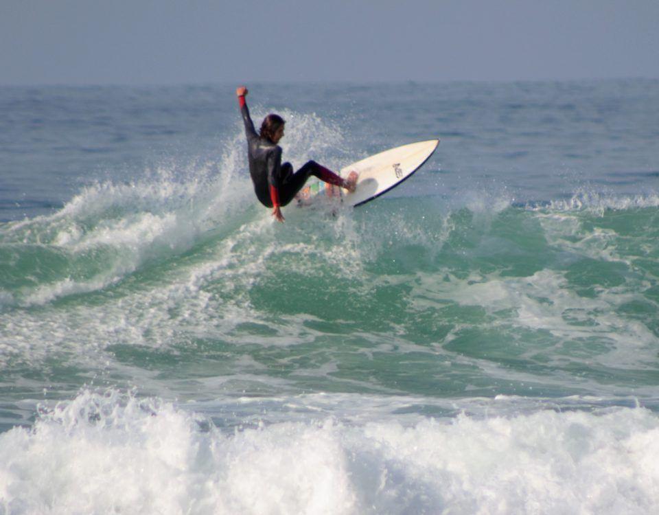 Alumno clase de surf avanzado cogiendo olas