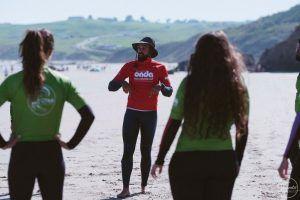 Profesor de surf dando directrices a alumnos