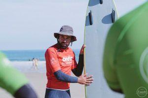 Profesor de surf con tabla en arena