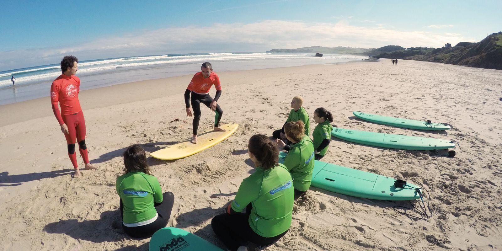Profesores de surf con alumnos en arena