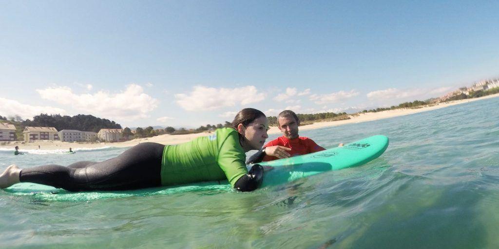 Profesor de surf con alumna en el agua