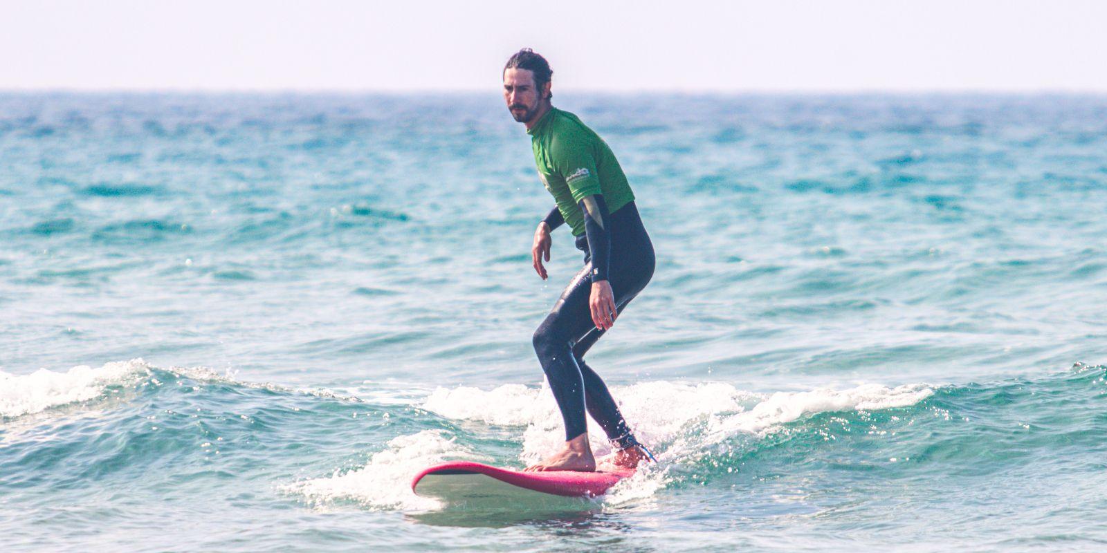 Alumno adulto sobre tabla en clase de surf