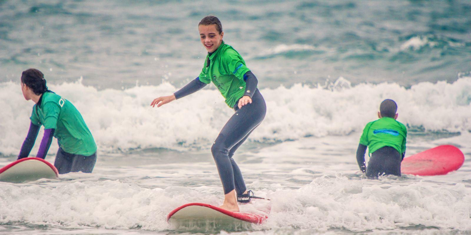Jóvenes aprendiendo surf en San Vicente de la Barquera