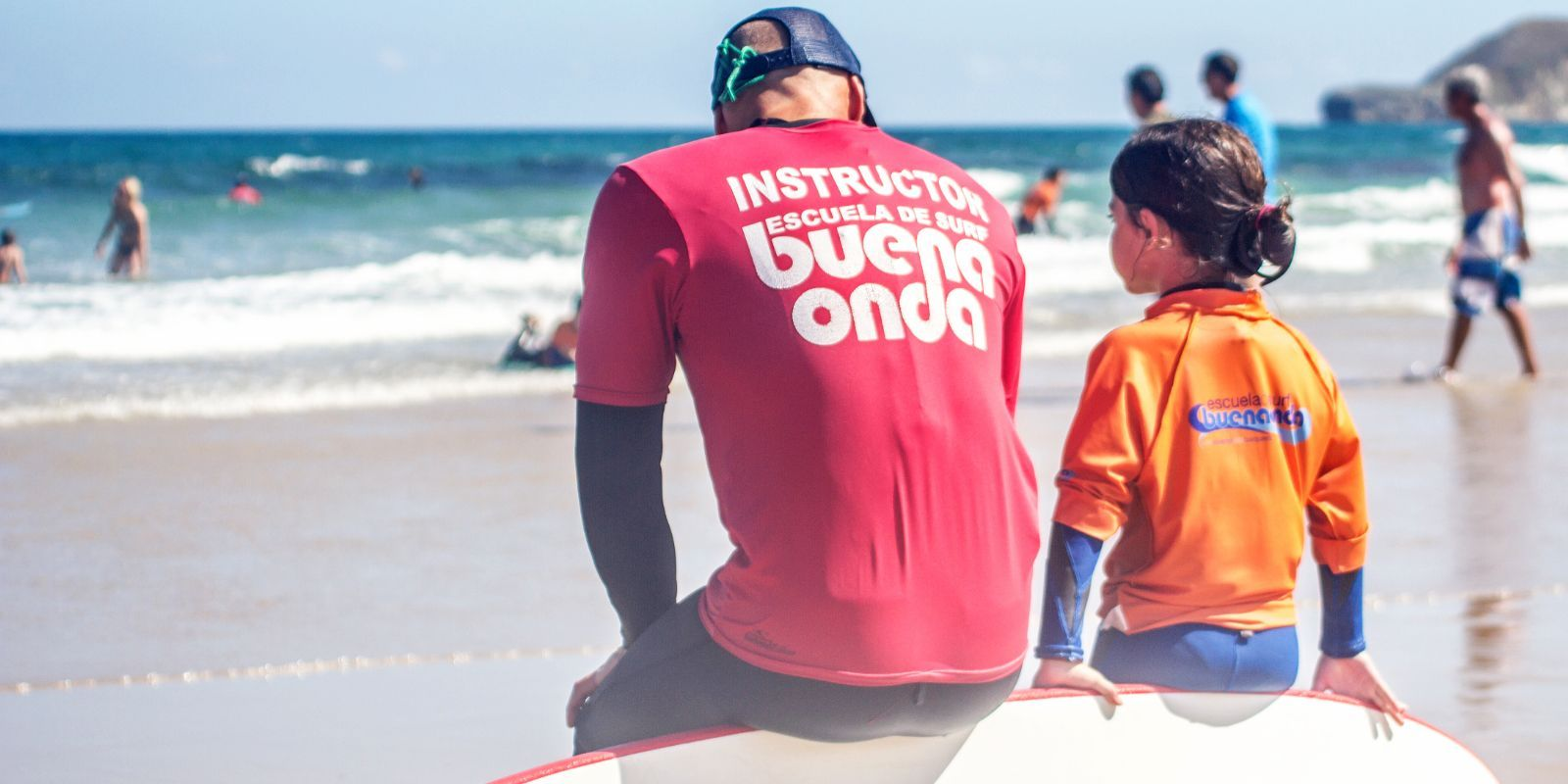 Profesor de surf sentado en tabla con alumna