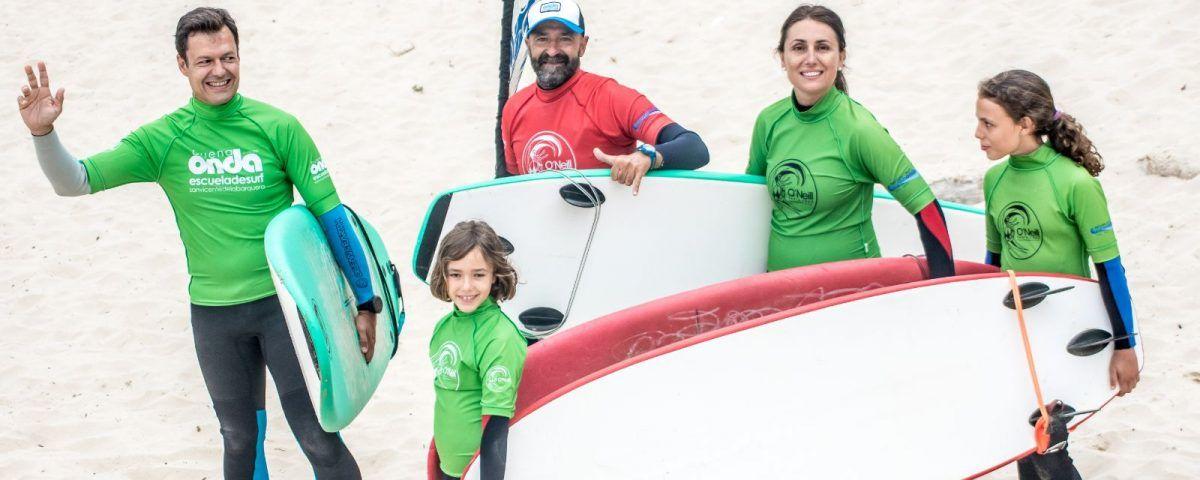 Profesor con familia en clase de surf privada