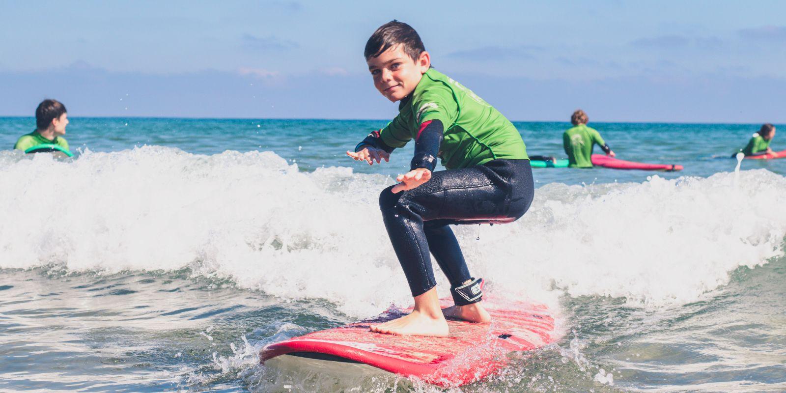 Niño sobre tabla en clase de surf